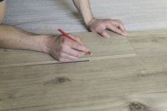 Carpenter worker installing laminate flooring in the room.  Stock Image