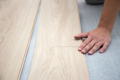 Carpenter worker installing laminate flooring in the room Stock Photo
