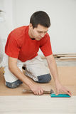 Carpenter worker joining parket floor. Carpenter worker installing wood parquet board during flooring work with hammer Royalty Free Stock Photos
