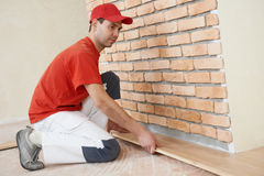Carpenter worker joining parket floor Royalty Free Stock Photos