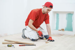 Carpenter worker joining parket floor Royalty Free Stock Images