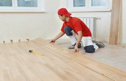 Carpenter worker joining parket floor. Carpenter worker installing wood parquet board during flooring work with hammer Stock Image