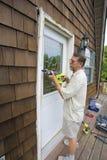 Carpenter working. Elderly carpenter replacing exterior door frames, weather has promoted Stock Image