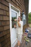 Carpenter working. Elderly carpenter replacing exterior door frames, weather has promoted Stock Photography
