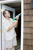 Carpenter working. Elderly carpenter replacing exterior door frames, weather has promoted Stock Photo