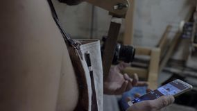 A carpenter in a working apron sets up a photo device through the application in the phone. man controls the camera through the. Phone. 4k. 4k video. 60 fps stock footage