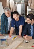 Carpenter Working On Blueprint With Colleagues Royalty Free Stock Photo