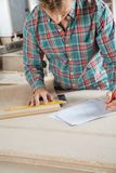 Carpenter Working On Blueprint While Measuring Royalty Free Stock Images