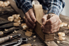 Carpenter working. In his workshop, he is smoothing a wooden board using a planer, carpentry, carpentry, woodworking and craftsmanship concept royalty free stock photo