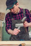 Carpenter working with a chisel. And hammer in a wooden workshop. Profession, carpentry and manual woodwork concept royalty free stock images
