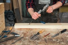 Carpenter working with a chisel. And hammer in a wooden workshop. Profession, carpentry and manual woodwork concept royalty free stock image