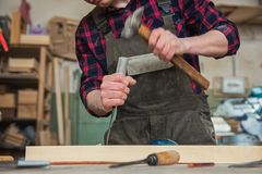 Carpenter working with a chisel. And hammer in a wooden workshop. Profession, carpentry and manual woodwork concept stock photography