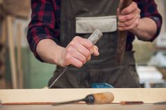 Carpenter working with a chisel. And hammer in a wooden workshop. Profession, carpentry and manual woodwork concept royalty free stock photography