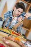 Carpenter working on craft in dusty workshop Stock Photos