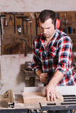 Carpenter working on an electric buzz saw cutting some boards Royalty Free Stock Photography