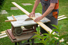 Carpenter working with electric buzz saw. Cutting wooden boards royalty free stock images