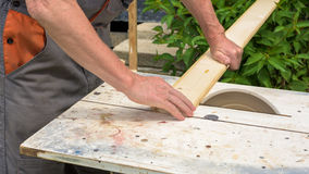 Carpenter working with electric buzz saw. Cutting wooden boards royalty free stock image