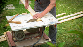 Carpenter working with electric buzz saw. Cutting wooden boards stock image