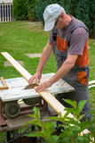 Carpenter working with electric buzz saw. Cutting wooden boards royalty free stock photos