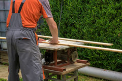 Carpenter working with electric buzz saw. Cutting wooden boards stock photo