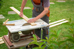 Carpenter working with electric buzz saw. Cutting wooden boards royalty free stock photography