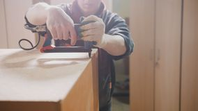 Carpenter working with an electric industrial stapler on the factory, fixing furniture details Royalty Free Stock Photography
