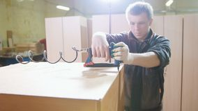 Carpenter working with an electric industrial stapler on the factory, fixing furniture details, close-up Royalty Free Stock Image