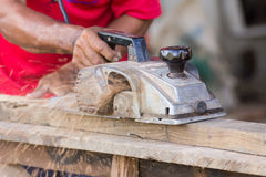 Carpenter working with electric planer Stock Photo