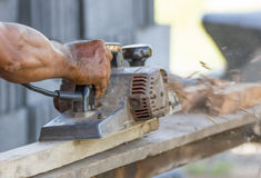 Carpenter working with electric planer Stock Image