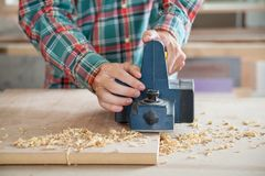 Carpenter Working With Electric Planer On Wood. Midsection of carpenter working with electric planer on wooden plank in workshop Stock Image