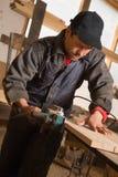 Carpenter working electric planer Royalty Free Stock Image