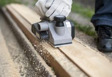 Carpenter working with electric planer on wooden plank in outdoor. Woodworking and craftsmanship concept stock images