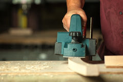 Carpenter working with electric planer. Carpenter working with electric planer on wooden plank in workshop Stock Photos
