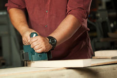 Carpenter working with electric planer. Stock Images