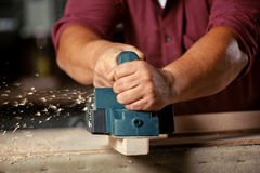 Carpenter working with electric planer. Royalty Free Stock Images