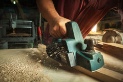 Carpenter working with electric planer. Royalty Free Stock Photos