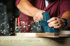 Carpenter working with electric planer. Royalty Free Stock Image