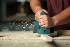 Carpenter working with electric planer. Stock Photography