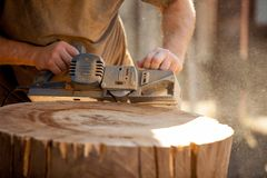 Carpenter working with electric planer on wooden stump outdoors stock image