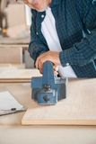 Carpenter Working With Electric Planer In Workshop. Midsection of carpenter working with electric planer in workshop Stock Photo