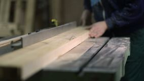Carpenter working on electric saw cutting boards stock video footage