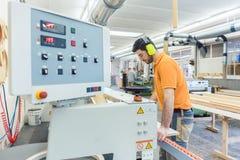 Carpenter working in furniture factory on machine stock photo