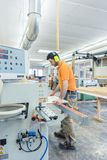 Carpenter working in furniture factory on machine stock image