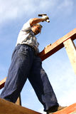 Carpenter working with hammer. On the top of a buiding Stock Image