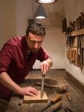 Carpenter working hard with tools in his carpentry Royalty Free Stock Image