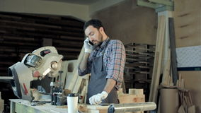 Carpenter working on his craft in a dusty workshop and speak phone. stock footage