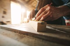 Carpenter working at his workbench. Close up of hands of senior carpenter doing some markings on wooden bar with measuring tape and pencil royalty free stock images