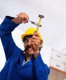 Carpenter Working in a Home. A bottom view of a carpenter working in a home. He is wearing a blue jumpsuit, yellow hardhat and safety goggles Royalty Free Stock Photography