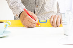 Carpenter working with level equipment and wood pencil in his  hand on white table. 1 Stock Photography