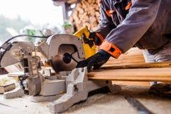 Carpenter working. Man cutting plank by circular saw. Stock Images